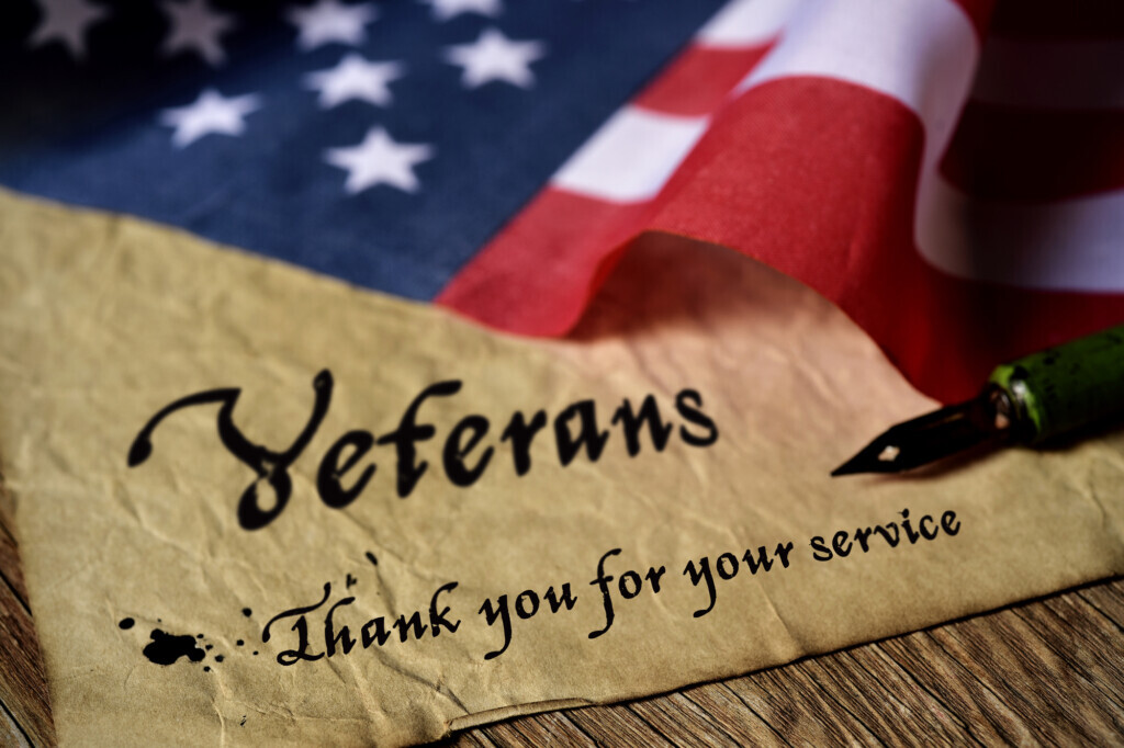 American Flag laying on brown paper with the words Veterans thank you for your service and a fountain pen